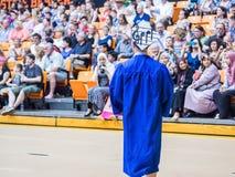 Szkoła średnia absolwent z muzycznymi notatkami na jego moździerz desce chodzi w kierunku widowni Fotografia Royalty Free