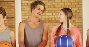 Szkoła średnia dzieciaki stoi wpólnie w boisko do koszykówki z koszykówką zbiory wideo