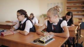 Szkoła średnia ucznie wykonują testowanie Niegrzeczny uczeń rozprasza uwagę dzieci w klasie i rzuca papierowego samolot w górę zbiory wideo