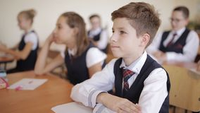 Szkoła średnia ucznie z mundurka szkolnego obsiadaniem w sali lekcyjnej i attentively słuchać wykład zbiory