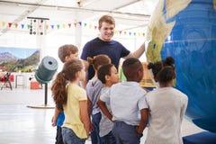 Szkoła żartuje patrzeć gigantyczną kulę ziemską przy nauki centre zdjęcie royalty free