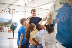 Szkoła żartuje wskazywać przy gigantyczną kulą ziemską przy nauki centre fotografia royalty free