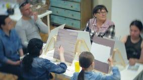 Szkoła artystyczna, twórczość i ludzie pojęć, - grupa ucznie z sztalugami, paintbrushes i paletami, maluje wciąż życie zbiory wideo