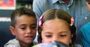 Szkoła dzieciaki dyskutuje na kuli ziemskiej w sala lekcyjnej zdjęcie wideo