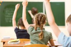 Szkoła dzieciaki w sala lekcyjnej przy lekcją zdjęcia royalty free