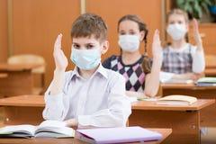 Szkoła dzieciaki z ochrony maską przeciw grypowemu wirusowi przy lekcją w sala lekcyjnej zdjęcie royalty free