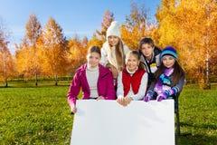 Szkoła dzieciaki z pustą plakat deską Zdjęcia Stock