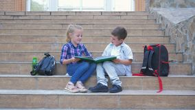 Szkoła, mali koledzy z klasy siedzi na krokach podczas przerwy outdoors z plecakami i widoków obrazki w książce,