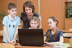Szkoła nauczyciel przy laptopem w sala lekcyjnej i dzieciaki zdjęcie stock