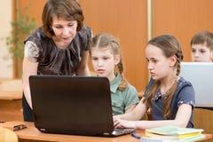 Szkoła nauczyciel przy laptopem w sala lekcyjnej i dzieciaki obraz stock