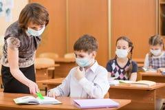 Szkoła nauczyciel z ochrony maską przeciw grypie i dzieciaki Obraz Royalty Free