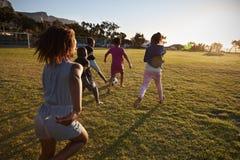 Szkoła podstawowa żartuje bawić się futbol w polu, tylny widok fotografia stock