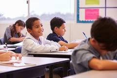 Szkoła podstawowa żartuje działanie przy ich biurkami w sala lekcyjnej fotografia royalty free