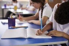 Szkoła podstawowa żartuje writing przy dziedzic biurkami, zakończenie up obrazy royalty free