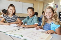 Szkoła podstawowa dzieciaki w klasowy ono uśmiecha się kamera, zamykają up obraz royalty free