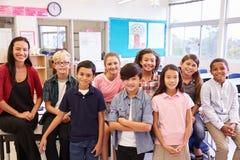 Szkoła podstawowa nauczyciel i jej ucznie w sala lekcyjnej obraz stock