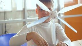 Szkoła podstawowa uczeń studiuje alternatywną energię z silnikiem wiatrowym i panelem słonecznym zdjęcie wideo