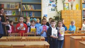 Szkoła podstawowa uczni stojak przed kamerą z książkami w ich rękach zbiory wideo