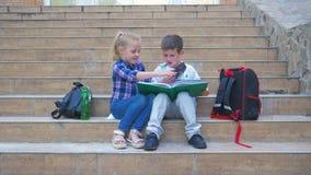 Szkoła podstawowa, ucznie siedzi na krokach i leafing przez książki podczas recesji outdoors z plecakami