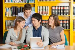 Szkoła wyższa przyjaciele Z Cyfrowej pastylki studiowaniem Wewnątrz Zdjęcia Royalty Free