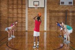 Szkoły średniej chłopiec wokoło brać karę strzelającą podczas gdy bawić się koszykówkę Fotografia Royalty Free