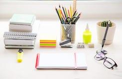 Szkoły lub biura stół blisko okno Dostawy i otwarty notatnik Zdjęcie Stock