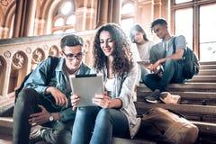 Szkoły wyższa życie Grupa ucznie używa pastylkę w uniwersytecie podczas gdy siedzący na schodkach obrazy royalty free