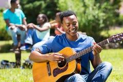 Szkoły wyższa chłopiec bawić się gitarę Zdjęcia Royalty Free