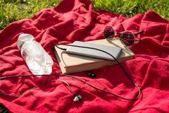 Szkocka krata w parku - butelka woda, książka, telefon z hełmofonami, okulary przeciwsłoneczni Relaksuje w miasto parku fotografia stock