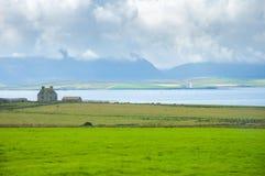 Szkocki zieleń krajobraz, gospodarstwo rolne i latarnia morska w morzu, trzymać na dystans w plecy Fotografia Stock