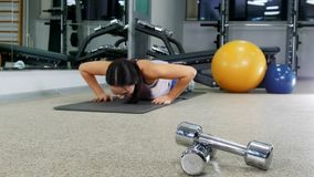 szkolenie Młoda kobieta ups w gym robić pcha Dumbbells na przedpolu zdjęcia royalty free
