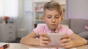 Szkolna chłopiec bawić się smartphone grę zamiast rysuje, gadżetu nałóg, hobby zbiory
