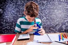 Szkolna chłopiec przy biurkiem z mikroskopem, duży blackboard Zdjęcia Stock