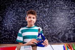 Szkolna chłopiec przy biurkiem z mikroskopem, duży blackboard Zdjęcie Royalty Free