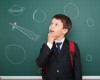 Szkolna chłopiec rysuje astronautyczną rakietę na pokładzie Fotografia Royalty Free
