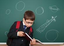 Szkolna chłopiec rysuje astronautyczną rakietę na pokładzie Obraz Royalty Free