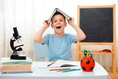 Szkolna chłopiec siedzi sali lekcyjnej łgarskiego biurko w domu wypełniał z książka stażowego materiału uczniem śpi gnuśnego zanu obrazy royalty free