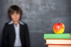 Szkolna chłopiec stoi blisko blackboard Zdjęcie Royalty Free