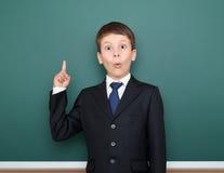 Szkolna chłopiec w czarnego kostiumu przedstawienia palca up gescie i cud, punkt na zielonym chalkboard tle, edukaci pojęcie fotografia stock
