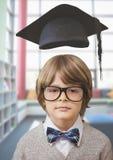 Szkolna chłopiec w edukaci bibliotece z skalowanie kapeluszem zdjęcie royalty free