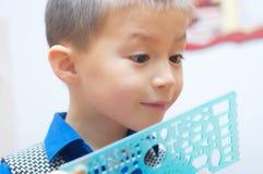 Szkolna chłopiec zadziwiająca z szkolnym materiałem Zdjęcia Royalty Free