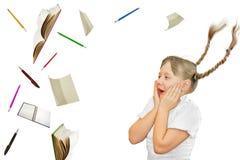 Szkolna dziewczyna patrzeje surpised przy szkolnymi przedmiotami Obrazy Royalty Free