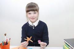 Szkolna dziewczyna pokazuje kwiaty od barwionego papieru na stole Fotografia Stock