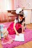 Szkolna dziewczyna robi pracie domowej Obrazy Royalty Free