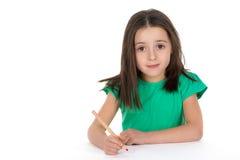 Szkolna dziewczyna rysuje obrazek używać kredkę Fotografia Stock