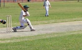 Szkolna krykiet chłopiec bawić się ciągnienie strzał Fotografia Stock