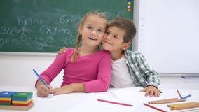 Szkolna miłość, koledzy z klasy pisze podczas lekcji przy stołem i wtedy patrzeje kamerę i uśmiech na tle blackboard zbiory