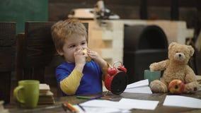 Szkolna przerwa Głodny dzieciaka łasowania jabłko w sala lekcyjnej Mała chłopiec bawić się z papieru samolotem Dzieciaka łasowani zbiory