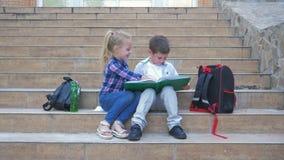 Szkolna przyjaźń, mali koledzy z klasy siedzi na krokach z plecakami i przegląd, rezerwujemy podczas przerwy w świeżym powietrzu