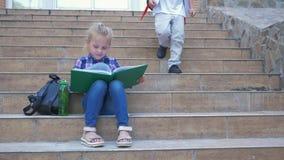 Szkolna recesja, żeński uczeń czyta książkowego obsiadanie na krokach z plecakiem, chłopiec kolega z klasy biega ona, i siedzimy
